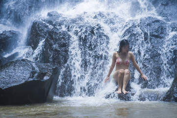 young beautiful and sweet Asian woman in bikini getting body wet under stream of natural amazing waterfall sitting on rock feeling purity