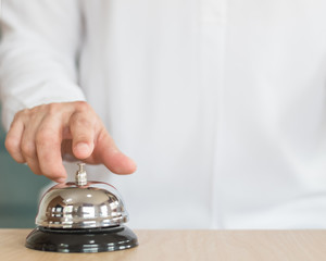 Hotel restaurant bell service on concierge customer reception counter with business person ringing pressing bell button calling for assistance
