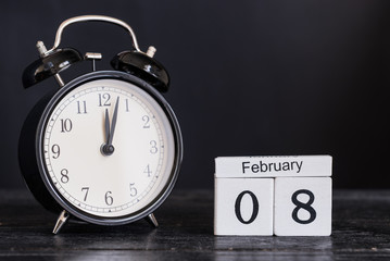 Wooden cube shape calendar for February 8 with black clock on black background. Copy space.