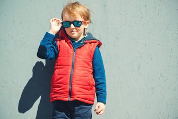 Cute blondy boy in a modern outerwear, outdoors.