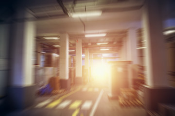Abstract industrial storage hall or warehouse in factory, plant or logistic company, motion blur effect with sun light