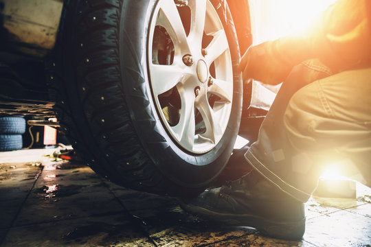 Wheel balancing or repair and change car tire at auto service garage or workshop by mechanic