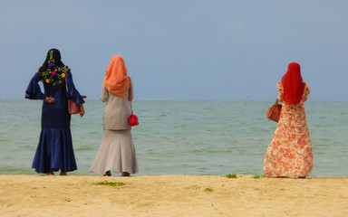 Three muslim women with colorful traditional clothes at Samila beach in Songkhla, Thailand