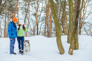 Couple in the winter wooden forest walking with a dog alaskan malamute. Holiday and freedom concept.