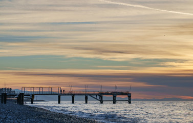 Pier silhouette in front of stripy sunset sky
