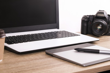 Photo blogger / photographer / it specialist's typical office space table with laptop, blank screen, coffee cup and electronics. Top view, copy space, flat lay, overhead, backdrop.