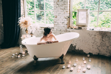 A beautiful boudoir morning of the bride, a pretty girl in a white man's shirt and underwear at a white bathroom with candles in glasses