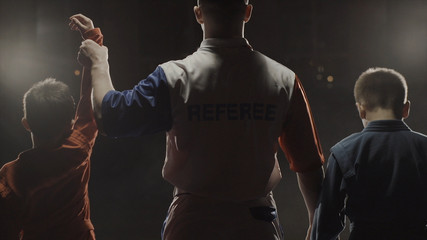 Rear view of the boys athletes and referee who raises the hand of the winner. The referee raises the hand of the boy winner in the ring. Judo