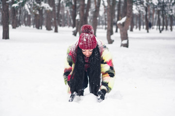 Girl collects snow with her hands