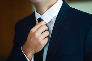 Grooms morning preparation, handsome groom getting dressed and preparing for the wedding, holding a tie in his hands