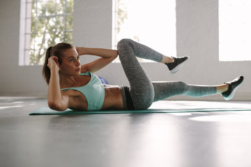 Woman in the gym doing sit-up exercise