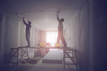 Workers are installing ceiling from wooden platform in apartment is under construction, remodeling, renovation, and reconstruction. Tone effect