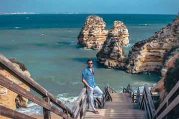 Foto op Aluminium Bali young man on vacation at the Algarve with cliffs and rocks on the beach