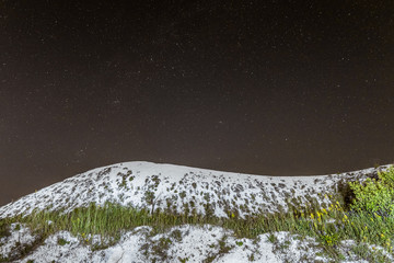 Starry night sky over the white cretaceous hill. Night natural scape with chalk ridge. Natural archaeological monument - Krapivenskoye ancient settlement, Belgorod region, Russia.