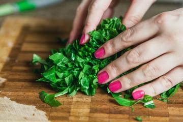 Hands of woman stirring green leaves of arugula