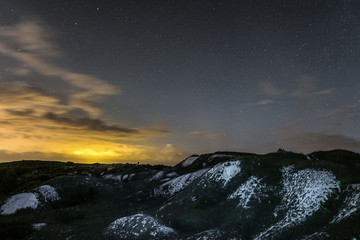 Night landscape with chalk ridges under cloudy and starry sky. White cretaceous hills at night. Natural archaeological monument - Krapivenskoye ancient settlement, Belgorod region, Russia.