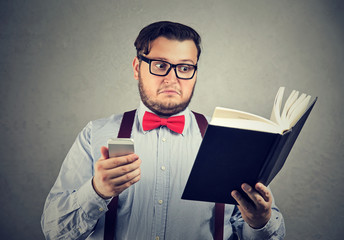Puzzled man confused with book and phone