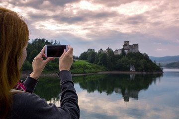 girl making a photo shoot of castle niedzica