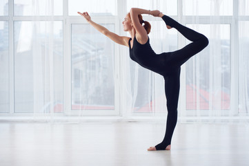 Beautiful young woman practices yoga asana Natarajasana - Lord Of The Dance pose at the yoga studio
