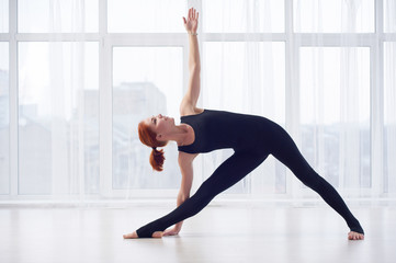 Beautiful young woman practices yoga asana Parivritta Trikonasana at the yoga studio