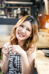 asain beauty girl happy in checker dress smiling with hot cofee in coffee shop