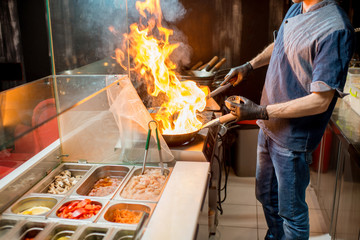 Chief cook cooking on the wok pan with flambe on the asian restaurant kitchen
