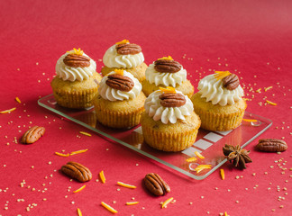 Cupcakes decorated with pecan nuts, orange zest and spice on red background