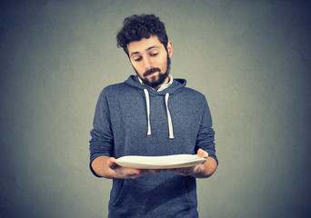 Man with empty plate looking sad