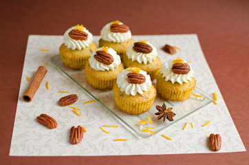 Cupcakes decorated with pecan nuts, orange zest and spice on brown background