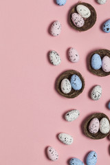 Easter eggs in a nest on a pastel pink background