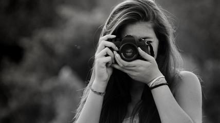 Ragazza che fotografa con macchina fotografica analogica vintage