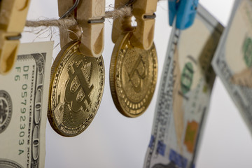Money laundering concept. Yellow clothes peg hold Bitcoin and one hundred dollar banknotes
