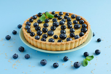 Lemon tartlet decorated with blueberries and mint on blue background