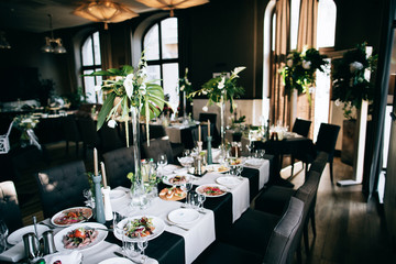 Beautiful black Wedding table decoration with fresh flowers in the restaurant