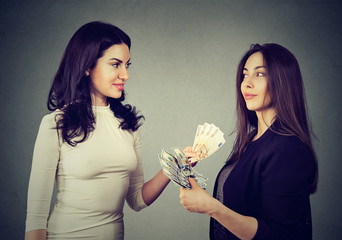 Content business women exchanging money