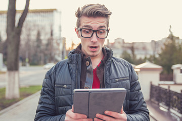 Shocked man watching tablet on street