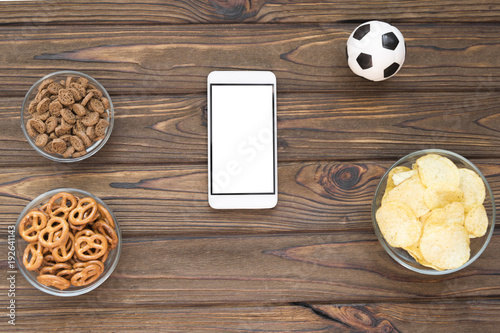 chips crackers snacks a smartphone a soccer ball on a wooden
