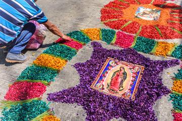 Decorating dyed sawdust Holy Thursday carpet, Antigua, Guatemala