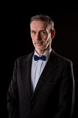 The older businessman in a suit with a bow tie on black background
