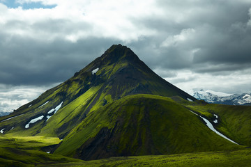 Free standing volcanic mountain covered with green moss
