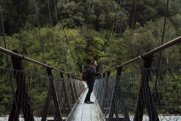 Hombre joven posando frente a un bosque en un puente de madera