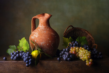 Still life with grapes in the basket and jug