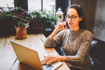 Theme is small business. A young freelance woman working behind a laptop computer in a coffee shop decorated with Christmas decor and talking on the phone. Dressed in a gray sweater and glasses