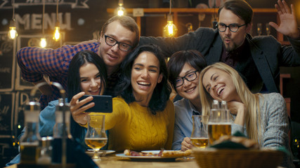 In the Bar/ Restaurant Hispanic Woman Takes Selfie of Herself and Her Best Friends. Group Beautiful Young People in Stylish Establishment.