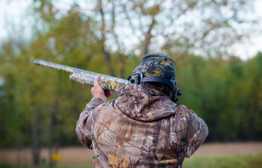 horizontal image of man trap shooting in camo with shotgun. Clay pigeons. selective focus. trap shoot, hat, long gun