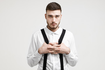 Waist up shot of serious confident young European macho man with bristle standing against white studio wall background, dressed in formal shirt, crossing hands on his chest, pulling suspenders
