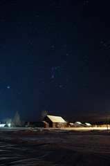 Constellation of Orion over an abandoned , old, rural club in Russian farms winter, frosty at night.