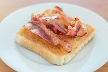 Fried bacon on toast on white plate.