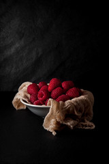 fresh ripe raspberries on a napkin and slate plate kitchen table can be used as background