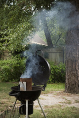 Charcoal starter smoking on a grill